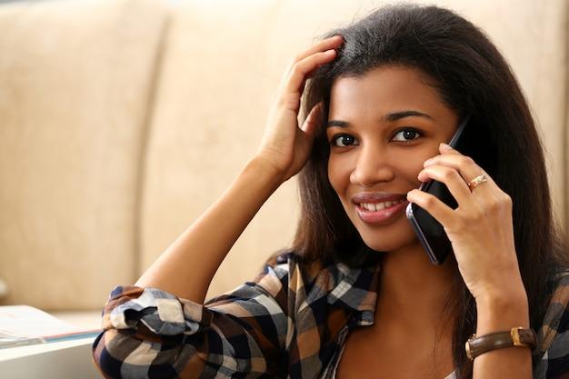 Uśmiechnięty murzynka chwyt w ręka telefonie komórkowym w domu