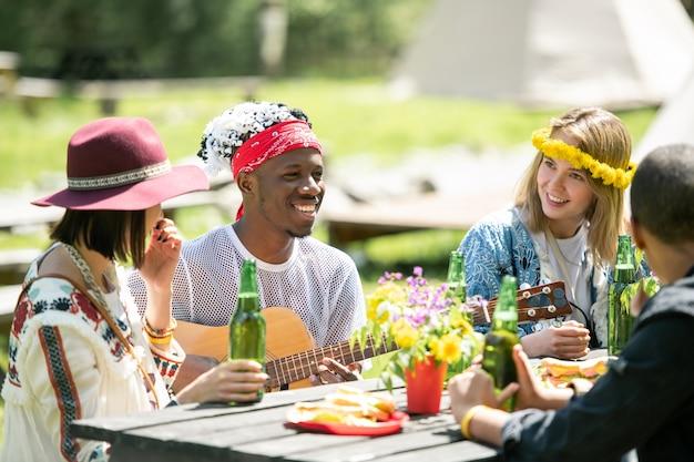 Uśmiechnięty muzyk gra na gitarze, siedząc z przyjaciółmi przy jednym stole na zewnątrz