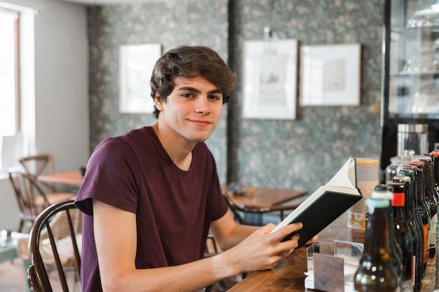 Uśmiechnięty nastolatek z książką przy kawiarnia kontuarem