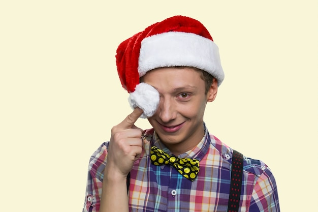 Uśmiechnięty nastolatek zamyka oko pomponem w mikołajowym kapeluszu. wesołych świąt. dobrze ubrany chłopak z muszką na białym tle na żółtym tle.