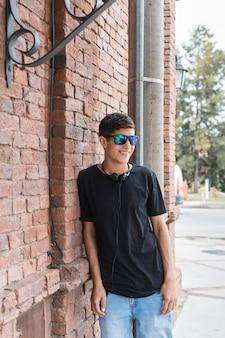 Uśmiechnięty nastoletni chłopak opiera na ściana z cegieł