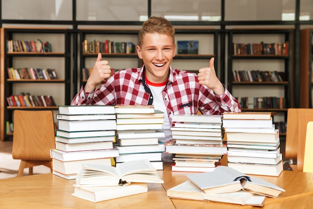 Uśmiechnięty nastoletni chłopak siedzi przy stole w bibliotece