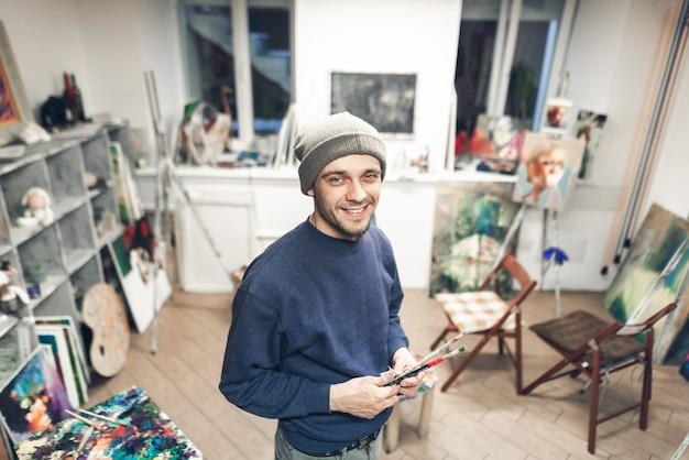 Uśmiechnięty nauczyciel malarstwa na tle pracowni artystycznej