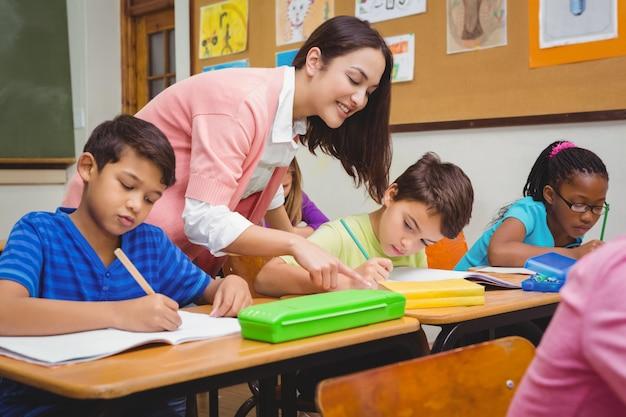 Uśmiechnięty nauczyciel pomaga studentowi