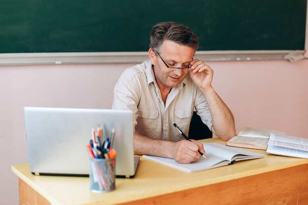 Uśmiechnięty nauczyciel w średnim wieku w okularach uważnie pisze.