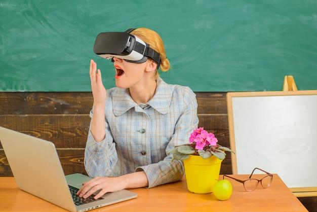 Uśmiechnięty nauczyciel w zestawie słuchawkowym vr z powrotem do szkoły nauczyciel edukacji online z koncepcją edukacji na laptopie