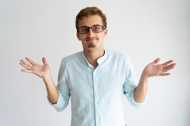 Uśmiechnięty nieostrożny blondynka faceta seans no zna gesta.