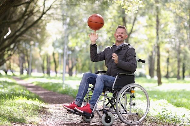 Uśmiechnięty niepełnosprawny mężczyzna kręci piłką do koszykówki na palcu siedząc na wózku inwalidzkim w parku