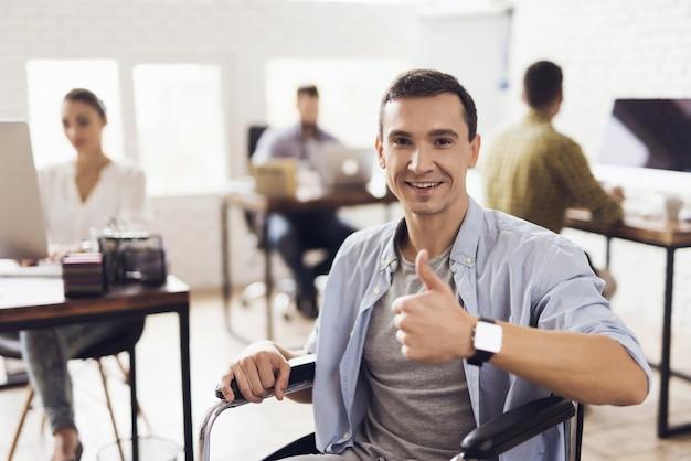 Uśmiechnięty niepełnosprawny mężczyzna na wózku inwalidzkim w biurze.