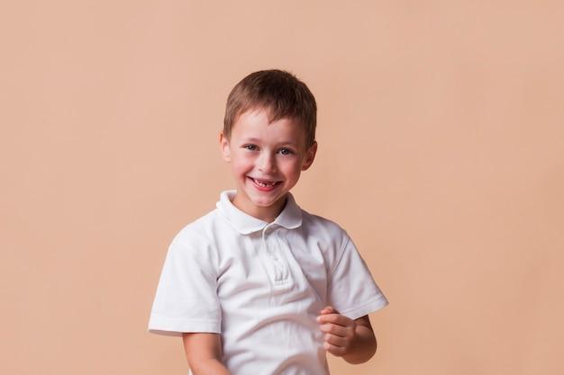 Uśmiechnięty niewinny chłopiec na beżowym tle