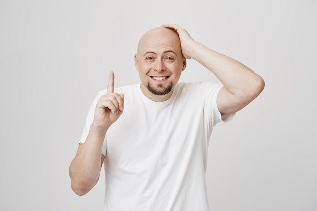 Uśmiechnięty niezręczny łysy facet wskazujący w górę i śmiejący się