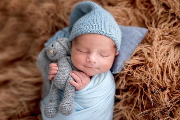 Uśmiechnięty noworodek trzymając dzianinową zabawkę w małych rączkach podczas snu