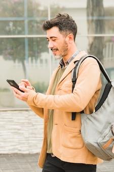 Uśmiechnięty nowożytny mężczyzna z jego plecakiem używać telefon komórkowego