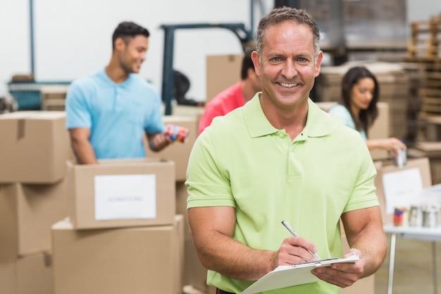 Uśmiechnięty ochotniczy mężczyzna bierze notatki trzyma schowek