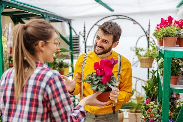 Uśmiechnięty ogrodnik sprzedający kwiaty klientowi stojąc w szklarni