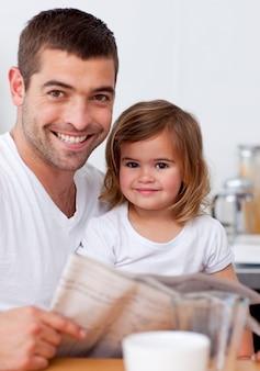 Uśmiechnięty ojciec czyta gazetę z jego córką