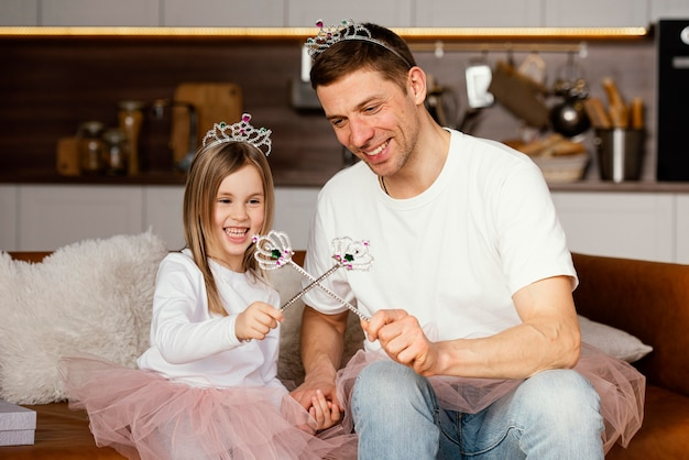 Uśmiechnięty ojciec i córka bawi się tiarą i różdżką