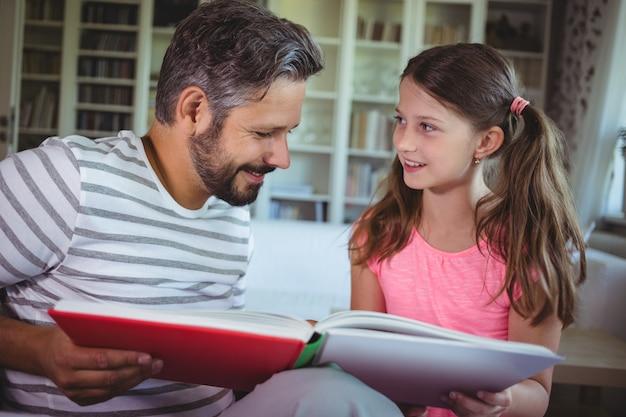 Uśmiechnięty ojciec i córka patrzeje album fotograficznego w żywym pokoju