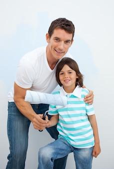 Uśmiechnięty ojciec i jego chłopiec paiting pokój