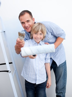 Uśmiechnięty ojciec i jego syna mienia paintbrush
