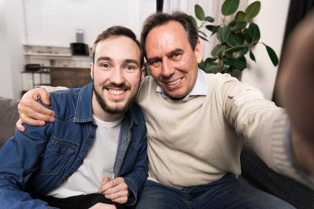 Uśmiechnięty ojciec i syn bierze selfie