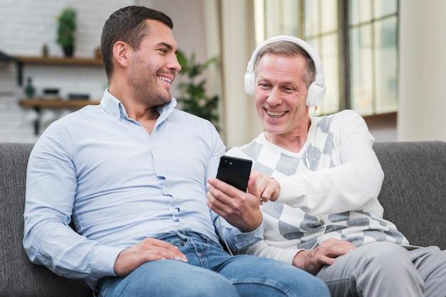 Uśmiechnięty ojciec i syn siedzi na kanapie