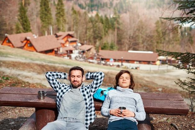 Uśmiechnięty ojciec i syn z zamkniętymi oczami odpoczywają na świeżym powietrzu