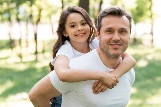 Uśmiechnięty ojciec piggybacking jego ślicznej córki przy parkiem