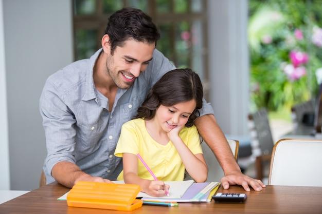 Uśmiechnięty ojciec pomaga córki z pracą domową