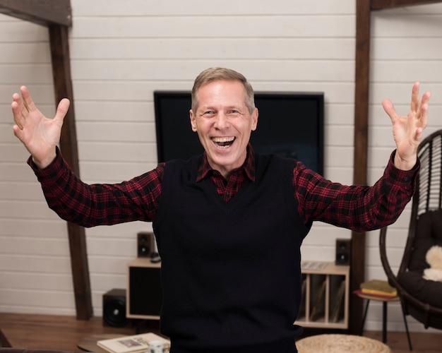 Uśmiechnięty ojciec pozuje z otwartymi rękami