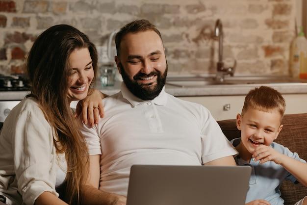Uśmiechnięty ojciec pracuje zdalnie na laptopie, podczas gdy jego syn i żona wpatrują się w ekran