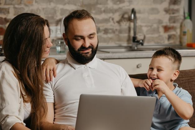 Uśmiechnięty ojciec pracuje zdalnie na laptopie, podczas gdy jego szczęśliwy syn i żona wpatrują się w ekran
