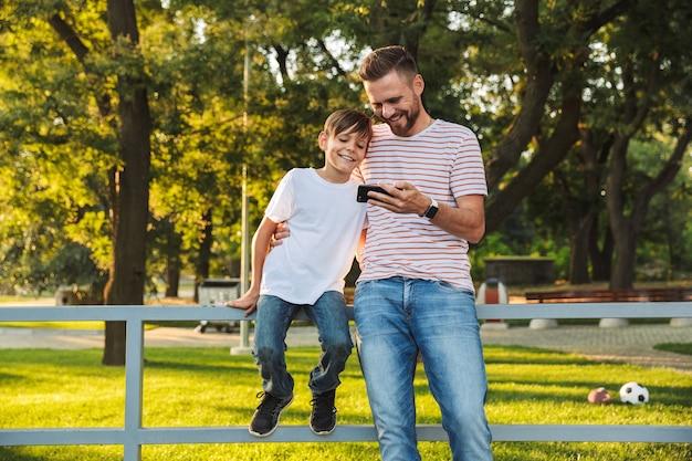 Uśmiechnięty ojciec spędzający czas ze swoim małym synkiem w parku