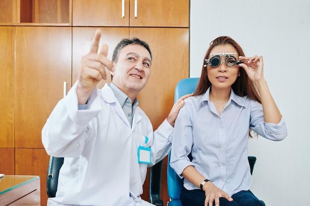 Uśmiechnięty okulista badający wzrok młodej pacjentki i proszący ją o przeczytanie listów na tablicy testowej