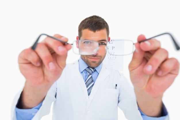 Uśmiechnięty okulista przedstawia eyeglasses