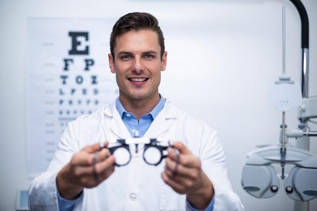 Uśmiechnięty okulista trzyma messbrille