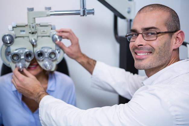 Uśmiechnięty optometrist egzamininuje żeńskiego pacjenta na phoropter