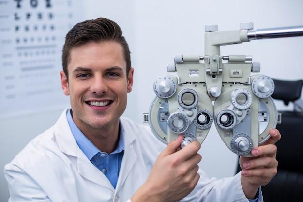 Uśmiechnięty optometrysta dostosowywa foroptera