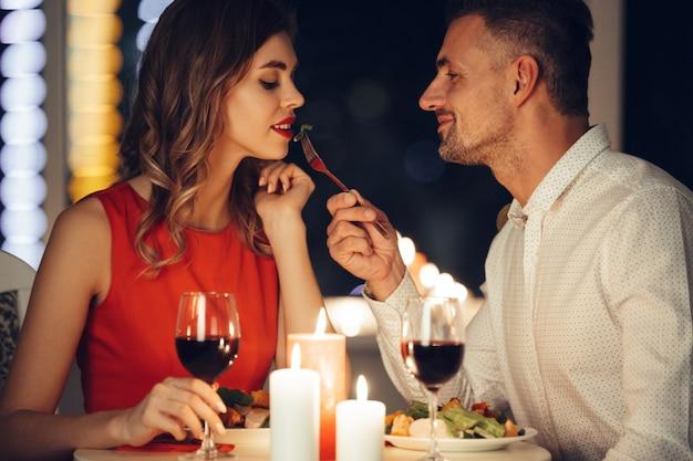 Uśmiechnięty ostrożny mężczyzna karmi swojego pięknego przyjaciela kobiety podczas romantycznej kolacji w domu