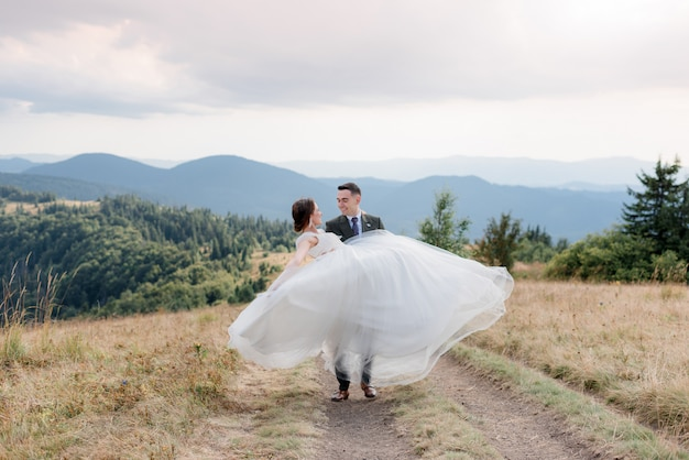 Uśmiechnięty pan młody niesie pannę młodą ubraną w białą suknię ślubną w słoneczny letni dzień w górach