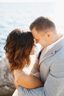 Uśmiechnięty pan młody przytula szczęśliwą pannę młodą, stojąc na skałach nad błękitnym morzem z góry