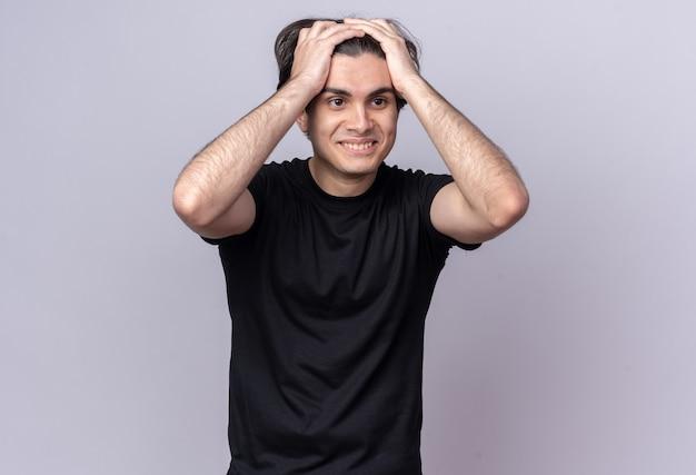 Uśmiechnięty patrząc na bok młody przystojny facet ubrany w czarną koszulkę chwycił głowę na białym tle na białej ścianie