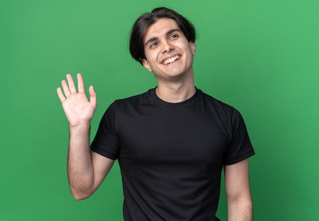Uśmiechnięty patrząc na bok młody przystojny facet ubrany w czarną koszulkę pokazujący gest powitania odizolowany na zielonej ścianie