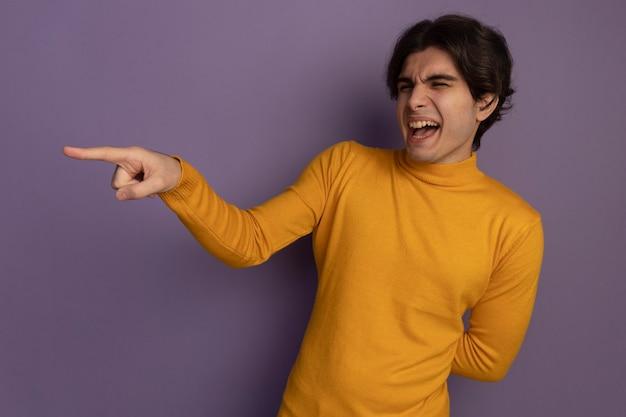 Uśmiechnięty patrząc na bok młody przystojny facet ubrany w żółty sweter z golfem wskazuje na bok trzymając rękę na talii na białym tle na fioletowej ścianie