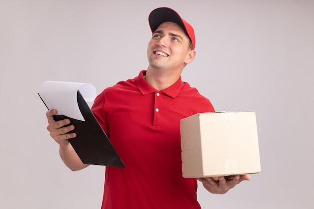 Uśmiechnięty, patrząc w górę młody człowiek dostawy ubrany w mundur z czapką, trzymając pudełko z schowkiem na białym tle na białej ścianie