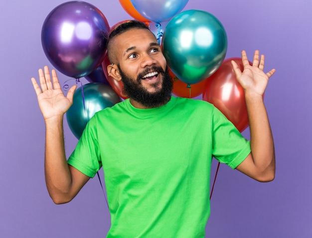Uśmiechnięty patrząc z boku młody afroamerykański facet ubrany w zieloną koszulkę stojący przed balonami rozkładającymi ręce izolowane na niebieskiej ścianie
