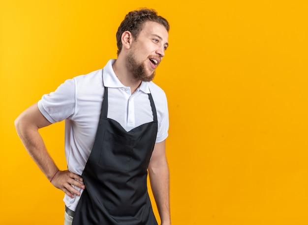 Uśmiechnięty patrząc z boku młody męski fryzjer ubrany w mundur kładący rękę na biodrze na białym tle na żółtym tle z kopią przestrzeni