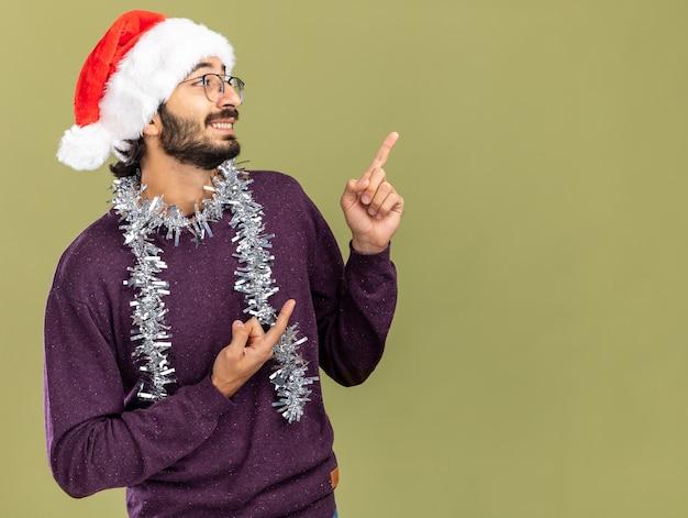 Uśmiechnięty patrząc z boku młody przystojny facet w świątecznym kapeluszu z girlandą na szyi wskazuje z boku na oliwkowozielonej ścianie z kopią miejsca