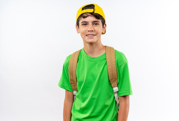 Uśmiechnięty patrzący aparat młody szkolny chłopiec ubrany w plecak z czapką