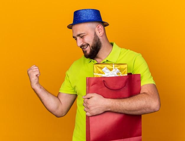 Uśmiechnięty patrzący boczny młody człowiek ubrany w imprezowy kapelusz trzymający torbę na prezent odizolowaną na pomarańczowej ścianie